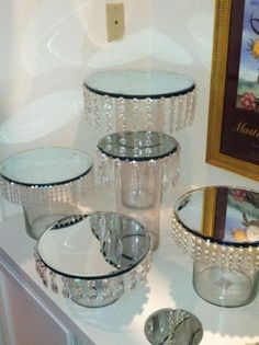 looks like they used dollar store vases and attached mirrors to the top then the jewels. I would spray paint cheap candlesticks silver and place in between the mirrors to create a cupcake stand - Crafts Are Fun Dollar Store Crafts, Dollar Stores, Thrift Stores, Diy Centerpieces, Centrepieces, Dollar Tree Centerpieces, Bling Centerpiece, Baby Shower Table Centerpieces, Candy Table