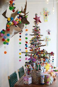 Un árbol de Navidad hecho de madera y decorado con pompones. La mejor forma de tener una celebración original y divertida.
