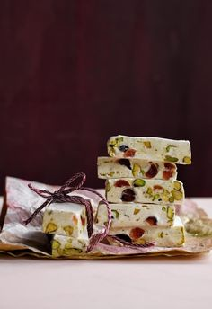 Pistachio and cherry nougat squares: Give the ultimate festive gift with bars of homemade nougat, packed with cherries and nuts, wrapped in candy-cane striped twine and delicate sheets of tissue paper. | 6 Christmas food presents to gift in 2018 | Styling: Steve Pearce | Photographer: Chris Court