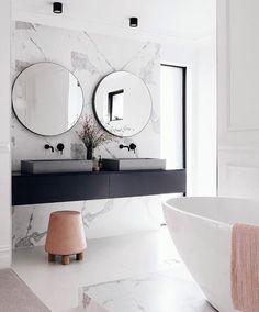 Badrum i marmor, svarta bänkar/kommoder och blandare med detaljer i rosa.