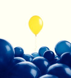 A yellow balloon rising above a group of blue balloons