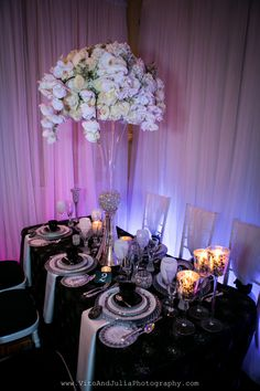 B&W tabletops with uplit drapes in hues of blue & purple.