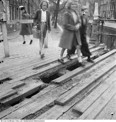 """1944-1945 - While the southern part of The Netherlands had been liberated by allied forces in September of 1944, people in the northern part of the country, including Amsterdam, had to live through """"The Hunger Winter"""". In the photo: With no food and coal to burn in their stoves the citizens of Amsterdam started to remove the planks from the wooden bridge throughout the city. #worldwar2 #Amsterdam #hongerwinter"""