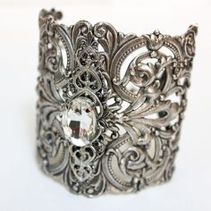 Product InfoProduct CareShippingThis ornate silver bridal cuff is truly amazing! The focal is a clear crystal in a filigree setting which compliments the lovely details and openwork of the base of the cuff. Almost wide, I have added c. Bridal Cuff, Bridal Bracelet, Bridal Jewelry, Bracelet Size Chart, Bracelet Sizes, Necklace Sizes, Necklace Lengths, Wire Wrapping Crystals, Small Gift Boxes