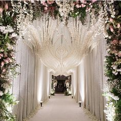 thebridestory  · www.bridestory.com Love this tunnel decoration for an engagement party. The cascading white flowery decoration that forms into a patterns makes a grand entrance to the ballroom.
