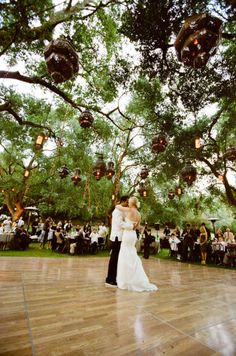 Wow! What a way to make a statement, so beautifully done with contrast of the high polish of the dance floor surrounded by the beautiful greens of the outdoors and lit up by morrocan lanterns hanging from the tree branches.