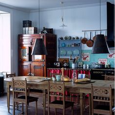 The ultimate example of an unfitted kitchen, the black work surface and lamps add an edge of grown-up glamour to this colourful eclectic scheme.