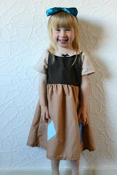 Snow White rags inspired dress. Featuring beige blouse with beige peter pan style collar, brown corset and a slightly darker beige skirt. Neckline features small black ribbon detail and skirt features two patches in shades of blue. Hair band and cuddly toy not included. The last picture in each listing is a size guide. As all children are different, please order according to this. While for the most part, pattern size is the same as child age, its always best to check a waist/chest measu...