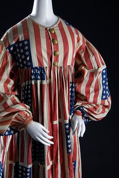 """American Flag"" costume - Printed cotton, metal buttons - Circa 1889,  USA. Costumes were commonly worn to parades and pageants during the 19th century and were intended to promote national identity and  patriotism. The flags on this costume contain 39 stars, most likely in  anticipation of the Dakota Territory attaining statehood, but the  territory was split into two states. Thus, this fabric lost its  original purpose—yet remains a unique, stylized design."