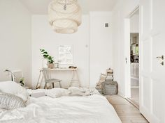 Workspace in bedroom: white trestle table, grey wooden chair, plants, framed art above desk, white bed linen, scatter cushions, pale wicker/straw pendant light, books stacked on floor, grey woven basket