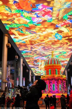 People look at a large screen at The Place, a shopping mall on December Eve in Beijing, China