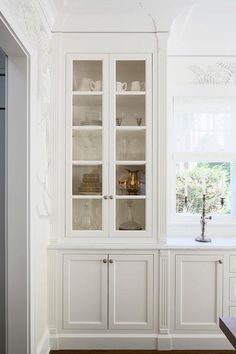 Chic dining room features a built-in sideboard topped with Lincoln Gold Vein Marble under three windows dressed in white bamboo roman shades flanked by glass front china cabinets.