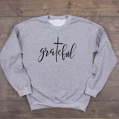 Grateful Christian Sweatshirt | Wear this Sweater with pride knowing that a % of your purchase goes towards spreading the word of God. Part will go to building new churches, and part will go to sending missionaries around the world. Our Grateful Christian Sweatshirt is not only adorable but extremely soft too! Its bold Message will be sure to turn heads! #christianapparel #womensfashion #winteroutfits #winterfashion #sweateroutfits #winteroutfits #sweater #womenssweater #valerymilano Christian Clothing, Christian Shirts, Christian Apparel, Girls Sweaters, Sweaters For Women, T Shirts For Women, Love Slogan, Jesus Clothes, Young Fashion