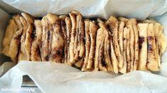Trhací buchta---Těsto 290 g hladké mouky 40 g moučkového cukru 5 g sušeného droždí 60 g másla 80 g mléka 60 ml vody 2 větší vejce půl lžičky soli  Náplň 60 g roztopeného másla 100 g třtinového cukru nebo krupicového 2 lžíce skořice 80 g pomletých vlašských ořechů ----plát o rozměrech přibližně 30 x 50 cm. potřeme rozpuštěným máslem, posypeme cukrem, skořicí a ořechy, rozřežeme na 6 stejně širokých pruhů, ty naskládáme na sebe a rozřízneme je opět na 6 stejně širokých obdélníků.