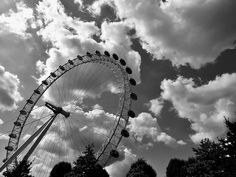 #amusement park #black and white #carnival #clouds #ferris wheel #fun #height #low angle shot #monochrome #perspective #rides #theme park