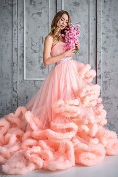 Beautiful young girl with long wavy hair holding a bouquet of fl - Beautiful young girl with long wavy hair holding a bouquet of flowers in a beautiful pink dress-the cloud is in a beautiful interior