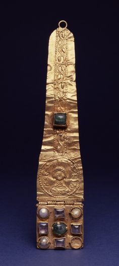 """6th-7th AD (Late Antique) Byzantine gold and (modern semi-precious) stones head ornament found in Izmir, Turkey.  Stones placed in 1910s to replace lost originals.  Held by Walters (Acc 57.546).  6 3/4"""" x 1 3/8"""" x 5/16"""" (17.1 x 3.5 x 0.8 cm).  Per Walters: """"May have been a hair ornament, or one of two pendants that hung from a noblewoman's crown or headdress. The small bust of a woman with a turreted crown is identified by the Greek inscription """"KOCMIA"""" as a personification of Adornment."""""""