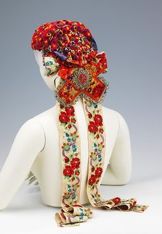 Headdress    Date:      1950–65  Culture:      Hungarian  Medium:      synthetic, metal, silk, cotton.  This headdress is an excellent example of folk traditions which were carried on through centuries. The use of celluloid in the flowers rather than traditional paper or textiles marks this as a later object; however it is otherwise traditional in form and decoration.
