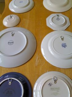 Hang plates with D-rings (found in hardware stores with other picture hanging stuff) and Gorilla Glue for 10 cents per plate, EVEN BETTER IDEA? gorilla glue POP CAN TABS to back of plates and hang from WIRE HANGERS bent into sheetrock hooks! upcycle your heart out