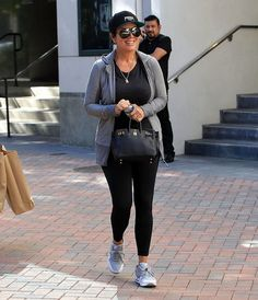 Kris Jenner in a black baseball cap, a gray hooded sweater, and Hermes Birkin bag.