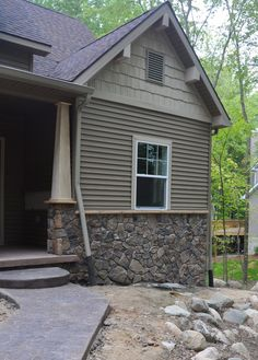 Front entry showing siding combination of cultured stone, vinyl siding and vinyl shake. Custom porch posts