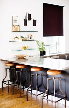 White kitchen with marble countertops, glass open shelves, and wood stools
