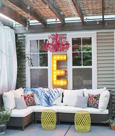 "Cheap and easy roof, funky chandelier, curtain for privacy, big ""S"" for ambient light, comfy DIY couch, funky tables/footstools. Yeah."