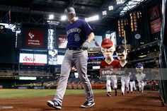 DJ LeMahieu #9 of the Colorado Rockies walks from the dugout as the 'Dbacks Legends' take the field during the fifth inning of the MLB game against the Arizona Diamondbacks at Chase Field on April 6, 2016 in Phoenix, Arizona.