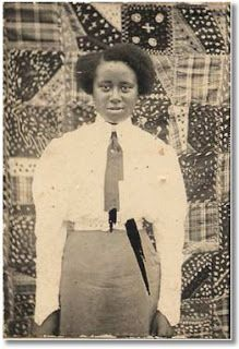 Posing for a serious portrait, with a family quilt hung as the backdrop   The Quilt Complex