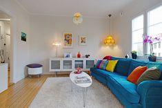 J'aime : l'amas de lampes dans le salon et le canapé bleu et ses coussins colorés