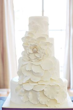 All white wedding cake with cascading petals