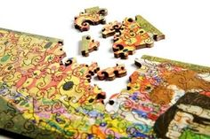 Klimt Hope wooden puzzle, with swirling shapes  http://www.artifactpuzzles.com/Artifact-Puzzles-Klimt-Hope-Wooden-Jigsaw/M/B002ML0WJE.htm