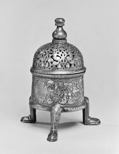 Syrian (Artist)  PERIOD  13th century (Medieval)  MEDIUM  brass with silver inlay  (Metal)  ACCESSION NUMBER  54.451  MEASUREMENTS  7 11/16 x 3 13/16 in. (19.5 x 9.7 cm) (h. x diam.) width at legs 5 5/16 in. (13.45 cm)  GEOGRAPHIES  Syria (Place of Origin)  This engraved and inlaid incense burner with a pierced top is decorated with birds on an arabesque background.