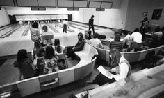This image shows students in a bowling alley in Plemmons Student Union, built 1967, at Appalachian State University (1967-current) in the 1970s. Students can be seen sitting on benches while one student throws a bowling ball. The alley was located in the current location of the Greenbrier Theater.