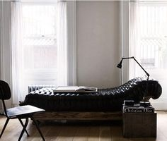 black chaise on wood base with modern lighting and vintage storage...