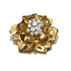 Yellow gold and diamond clip, Cartier, circa 1950 Of floral design, the pistil set with circular-cut diamonds, to the yellow gold petals