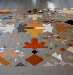 Pour repeindre le parquet de ce salon, un beau jeu de motifs réalisé avec quatre couleurs de peinture pour imiter un tapis au sol