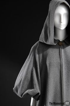 Coat (front view) | Madame Grès | France, 1947 | Grey wool twill | The day coat was a staple of the Grès oeuvre in the 1950's. This hooded gray version made of dense, brushed wool has a strong volumetric quality obtained from an elementary combination of two-dimensional, circular pattern pieces, rather than by molding the material into shape | The Museum at FIT, New York