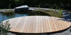 Naturpool kombiniert mit harmonischer Holzterrasse. Runder Holzsteg aus unbehandeltem Lärchenholz.