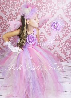 Melina Rainbow Dream Fairy Little Girls Tutu Dress Costume     What little girl doesn't dream of being a fairy? Oh she will love to wear beautiful wings and all magical things, a shiny dress and glittery wand! Our fairy costume features soft flowing tulle in Mint, Hot Pink & Lavender. Bodice is blooming with a premium silk lavender peony bloom.      Dress comes with matching pink leotard, tulle hair poof, Fairy Wings, Fairy wand and pretty white satin gloves.