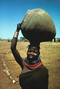 Africa | Woman carrying a jar on her head.  Uganda | Africa | Ugandan woman wearing bark cloth dress | ©Digital Library University of Wisconsin--Madison. African Studies Program.
