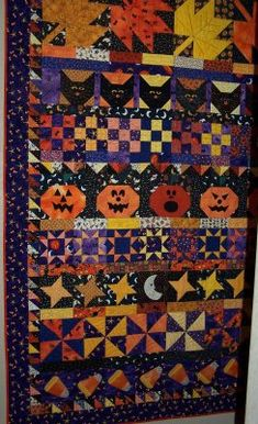 Really cool row quilt for Halloween with pumpkins, black cats, candy corn, jack o lanterns.