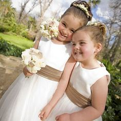 Flowergirls in white dresses with satin bodices and gathered tulle skirts with a satin ribbon around waist