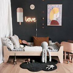 Super cute and cool girls room with Black feature wall and neon light