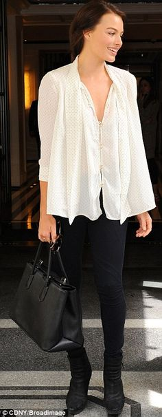 Off-duty style: The 23-year-old was dressed in a simple white blouse, black skinny jeans and boots and carried a large black handbag as she left her hotel