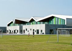Vibrant green stripes and angular roofs add character to the exterior of this school that architecture firm CEBRA has completed in Aabybro, Denmark.