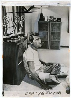 Rod Serling smokes a cigar at home, leaning against a bookcase adorned with three Emmys (1959)