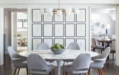 A Saarinen tulip table by Knoll is surrounded by vintage chairs in the kitchen. The chandelier is by Arteriors, and the artwork is made up of framed menus from dinners Kahng attended at restaurants Per Se and the French Laundry.