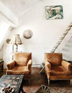 Armchairs in white living room with hexagon terra cotta floor tiles