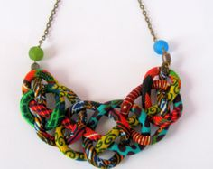 This gorgeous handmade Kente fabric bib necklace is designed with four tubes is very light and flexible. I also added a side knot that adds to its charm.The dominant color orange is a fashion trend and sits beautifully on the neck.  Length from one end to the other in a straight line is 18 inches or 47 cm.I have also added 3 inches or 8 cm extension chain. If you want a matching bracelet in the fourth picture https://www.etsy.com/listing/263124544/kente-african-bracel...